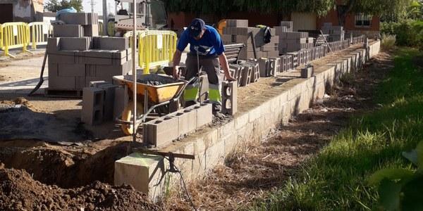 Operaris municipals construïnt el mur mitger